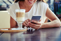 Woman using her smartphone in cafe. Portrait of attractive young woman using her smartphone in cafe Stock Photography