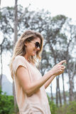 Woman using her smartphone. In the countryside Stock Photo