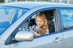 Woman using her smartphone while driving a car Stock Image