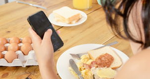 Woman using her smartphone while having breakfast. At home stock video