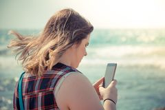 Woman using her smartphone outdoors at the beach near the sea.  Royalty Free Stock Photography