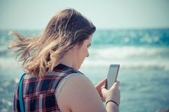 Woman using her smartphone outdoors at the beach near the sea.  Royalty Free Stock Photo