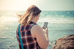Woman using her smartphone outdoors at the beach near the sea.  Stock Images