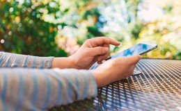 Woman using her smartphone outdoors. Woman using her smartphone at an outdoor cafe Royalty Free Stock Photo