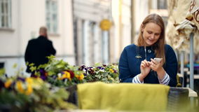 Woman using her smartphone sitting in outdoor cafe stock video
