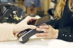 Woman using her smartphone to pay in a clothing store. Woman using her smartphone to pay in a clothing store, NFC technology. Mobile phone for shopping Royalty Free Stock Photos