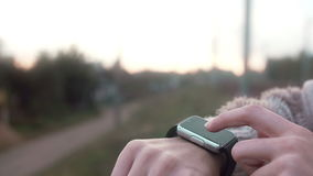 Woman using her smartwatch touchscreen device on a countryside background 4k. Woman using her smartwatch touchscreen portable technology device on a countryside stock video