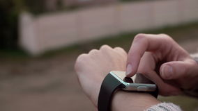 Woman using her smartwatch touchscreen device on a countryside background 4k. Woman using her smartwatch touchscreen portable technology device on a countryside stock video footage
