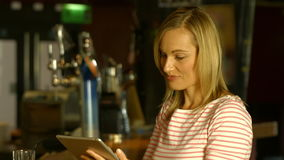 Woman using her tablet at the bar. In high quality 4k format stock footage