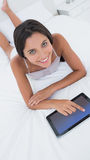 Woman using her tablet in bed Stock Images