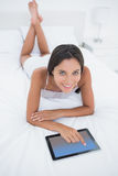 Woman using her tablet lying in bed Stock Image