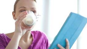 Woman using her touchpad. Young woman using her touchpad and drinking coffee sometimes being thoughtful or puzzled stock video footage