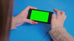 Woman using smartphone with green screen. Woman using horizontal smartphone with green screen. Close up shot of woman`s hands with mobile. Technology, chroma and stock video