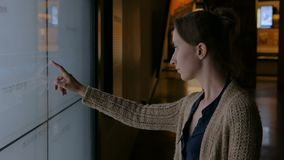Woman using interactive touchscreen display at modern jewish history museum stock video
