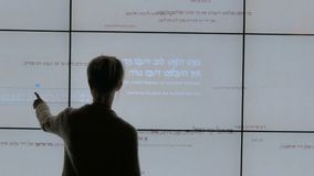 Woman using interactive touchscreen display at modern jewish history museum. Woman using interactive touchscreen display with biblical hebrew phrases at modern stock video