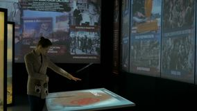 Woman using interactive touchscreen display at modern history museum. MOSCOW, RUSSIA - January 16, 2018: Modern Museum of Russia History. Woman using interactive stock video