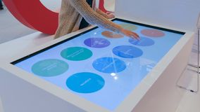 Woman using interactive touchscreen display at modern technology exhibition royalty free stock image