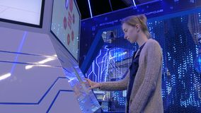 Woman using interactive touchscreen display at technology exhibition. Woman using interactive touchscreen stand and watching video presentation on large display stock video footage