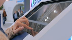 Woman using interactive touchscreen display at urban exhibition. Scrolling and touching. Education and technology concept stock footage