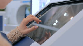 Woman using interactive touchscreen display at urban show. Woman using interactive touchscreen display at urban exhibition - scrolling and touching. Education stock footage
