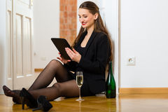 Woman using Internet for online Dating. Online Dating - Young businesswoman sitting at home on the floor while using a tablet computer for online dating Royalty Free Stock Images