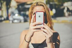 Woman using iPhone camera Royalty Free Stock Photos