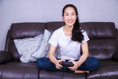 Woman using joystick controller playing video game on sofa in li Stock Images
