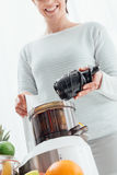 Woman using a juice extractor Stock Photo