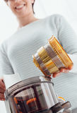 Woman using a juice extractor Royalty Free Stock Photos