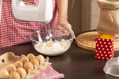 Woman using kitchen mixer. Detail of female hand holding mixer and mixing a pancake dough on the kitchen counter. Selective focus on the hand holding the bowl stock photos