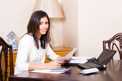 Woman using laptop. A pretty indian woman doing her finances with her laptop at a desk Stock Image