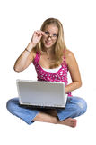Woman using a laptop. A young woman sits, cross-legged, with a laptop computer on her lap. She is putting on a pair of glasses royalty free stock images
