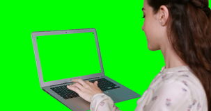 Woman using laptop. Against green screen stock footage