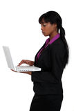 Woman using laptop. Attractive black woman using laptop isolated on white Royalty Free Stock Image