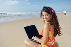 Woman using laptop at beach Stock Images