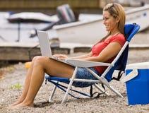 Woman using laptop on beach Royalty Free Stock Photos