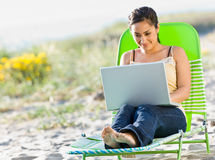 Woman using laptop at beach. Woman using laptop at the beach Royalty Free Stock Photography