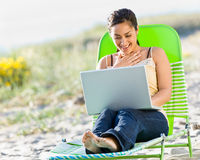 Woman using laptop at beach Stock Image