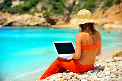 Woman using laptop on the beach Stock Photography