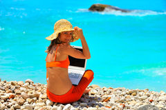 Woman using laptop on the beach Stock Images
