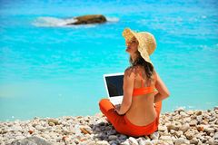 Woman using laptop on the beach Stock Photo