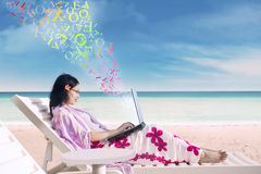 Woman using a laptop on the beach Stock Photo