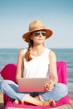 Woman using laptop on the beach Royalty Free Stock Photos