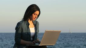 Woman using a laptop on the beach at sunset stock video