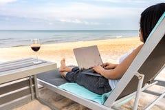 Woman using laptop on the beautiful beach stock photos