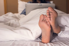 Woman using laptop on the bed Stock Images