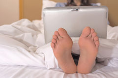 Woman using laptop on the bed Royalty Free Stock Images