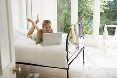 Woman Using Laptop In Bed Stock Images