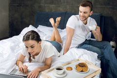 Woman using laptop in bed while man drinking coffee stock photos