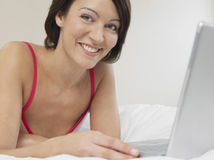 Woman Using Laptop In Bed Royalty Free Stock Image
